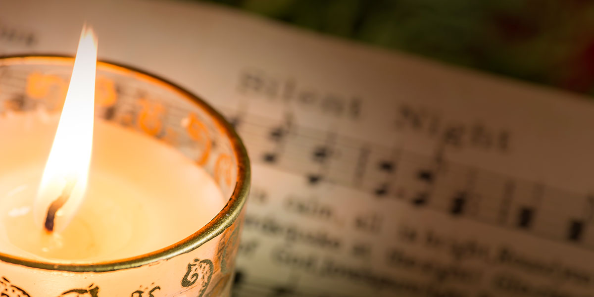 A lit candle in front of sheet music for Silent Night.