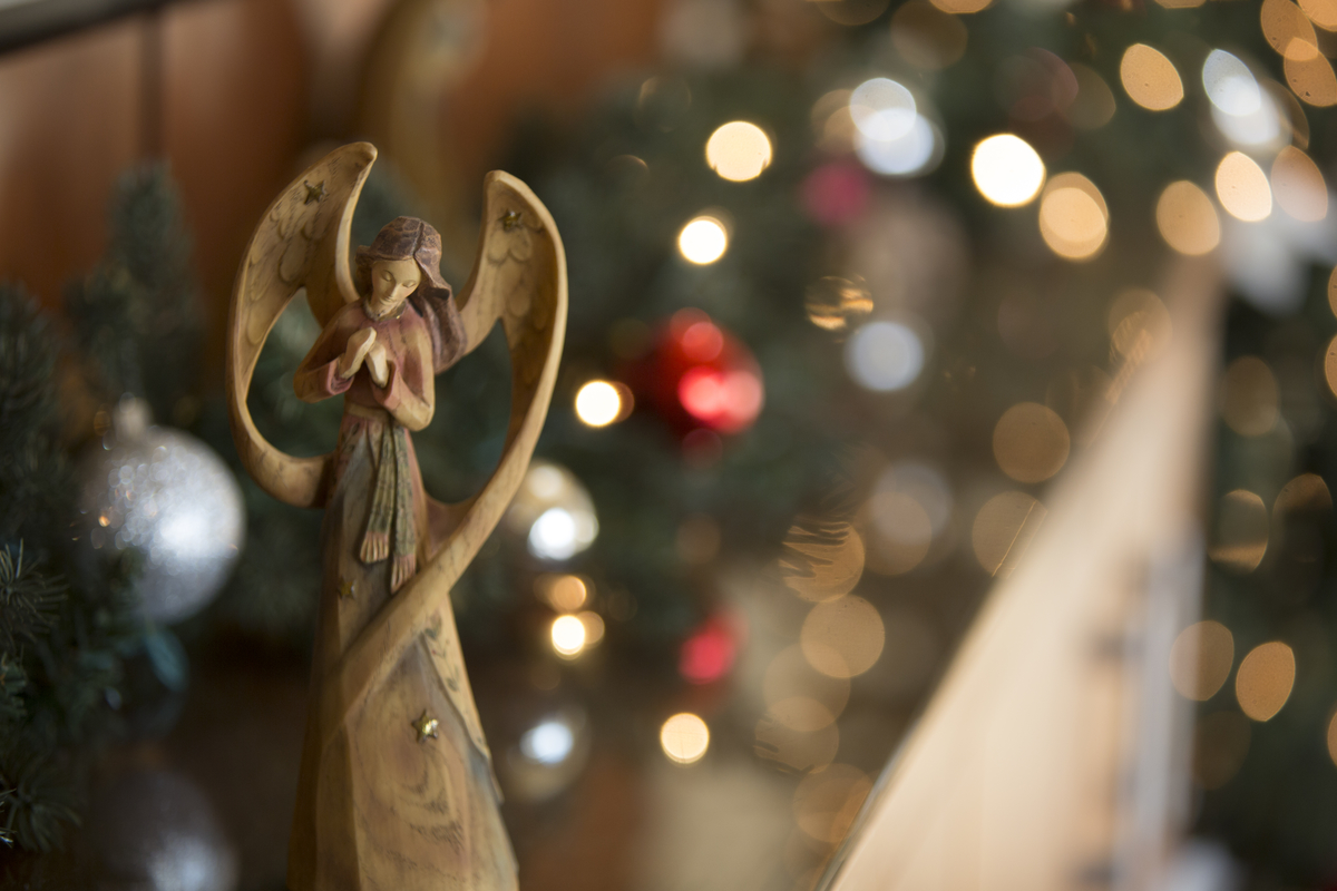 An angel Christmas ornament on a decorated tree.